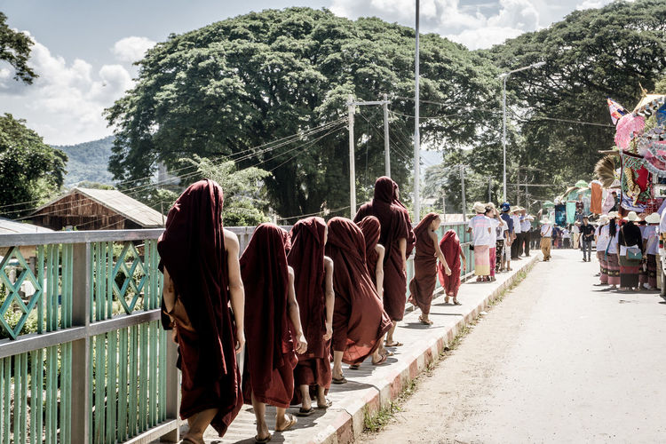Rear view of monks walking on footpath by road at city during sunny day