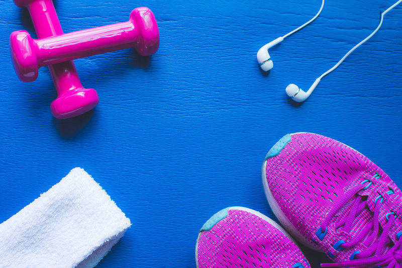 Fitness Equipment Dumbbell Pink Color Indoors  No People Close-up Still Life Weights Weight Sport High Angle View Exercise Equipment Exercising Sports Equipment Table Sports Training Blue Healthy Lifestyle Weight Training  Variation Purple Blue Background