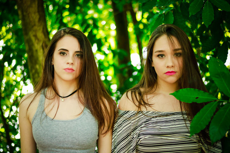 Beautiful Woman Close-up Day Focus On Foreground Front View Green Color Headshot Leaf Lifestyles Long Hair Looking At Camera Outdoors People Portrait Real People Tree Two People Young Adult Young Women
