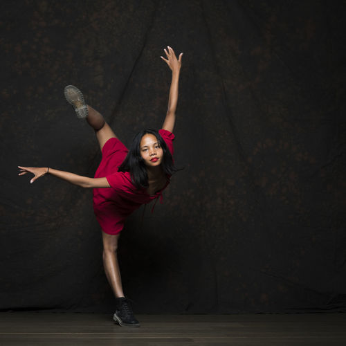 Full length of woman dancing on stage against black background