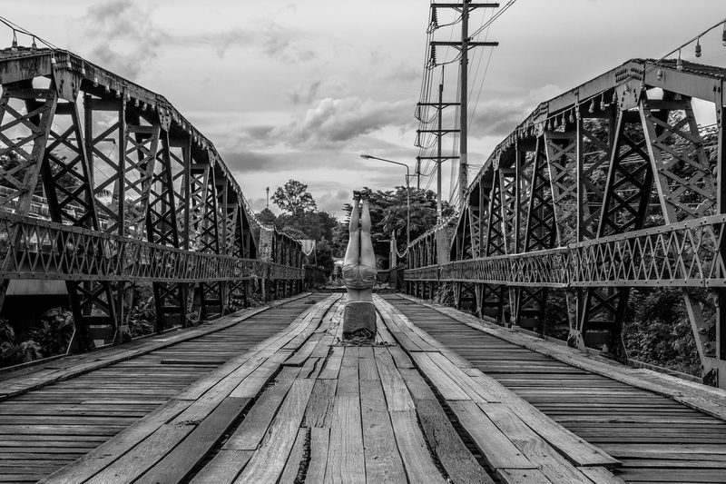 Rear View Of Woman Practicing Headstand On Wooden Footbridge Against Sky