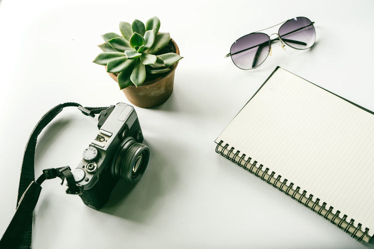 High angle view of camera with book and sunglasses on white background