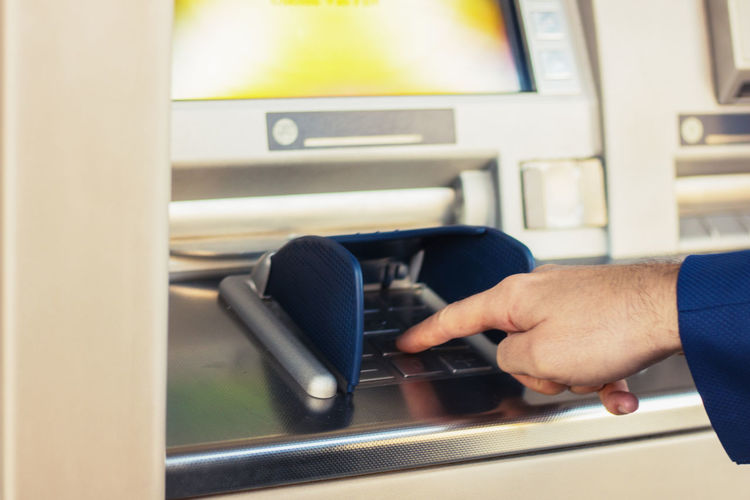 Cropped hand of man using atm machine