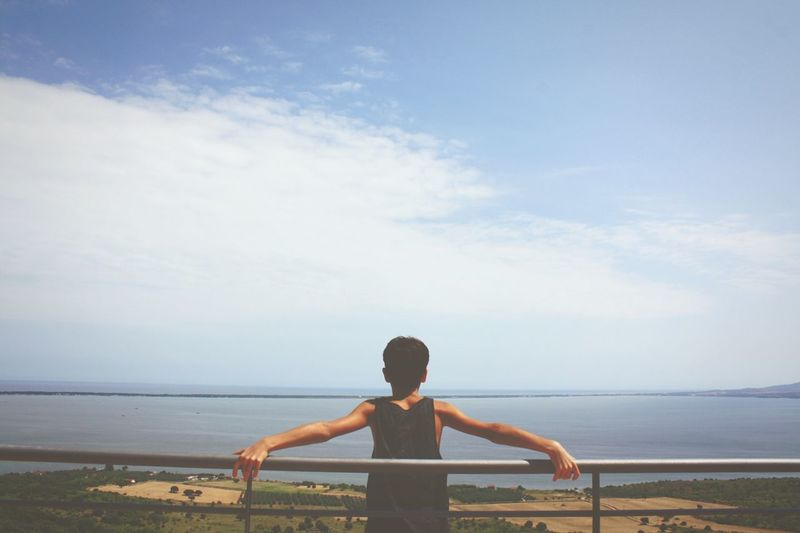 Rear view of boy bending while holding railing against sea