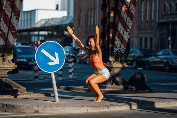 Woman with arms raised on street in city