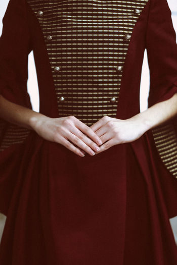 Female hands against the vintage dark red elegant dress