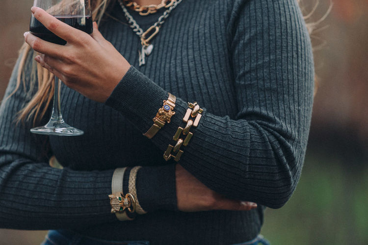 Midsection of woman in warm clothing wearing bracelet holding wineglass outdoors