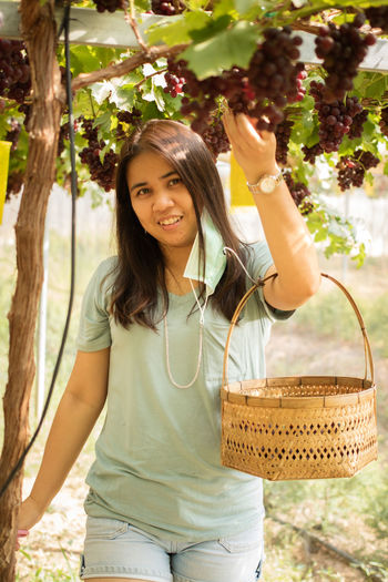 Portrait of smiling young woman holding basket against plants