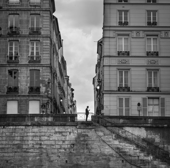 Man Standing Amidst Buildings Against Sky