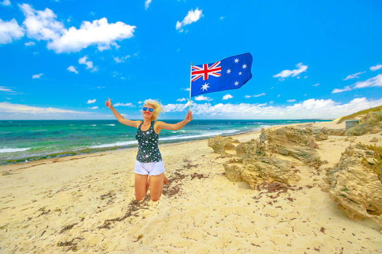 Woman holding australian flag jumping at beach
