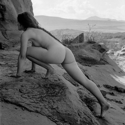 Naked woman crouching on rock at beach against sky