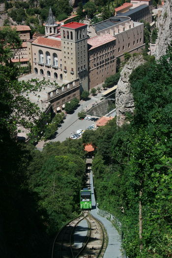"""Green """"zipper"""" tram going up the mountain with monastery on back ground. Monastery Montserrat Railroad Track Architecture Beauty In Nature Building Exterior Built Structure Cremallera De Montserrat Growth High Angle View Nature Plant Rail Transportation Railsway Scenics Transportation Zipper Train Been There. Done That."""