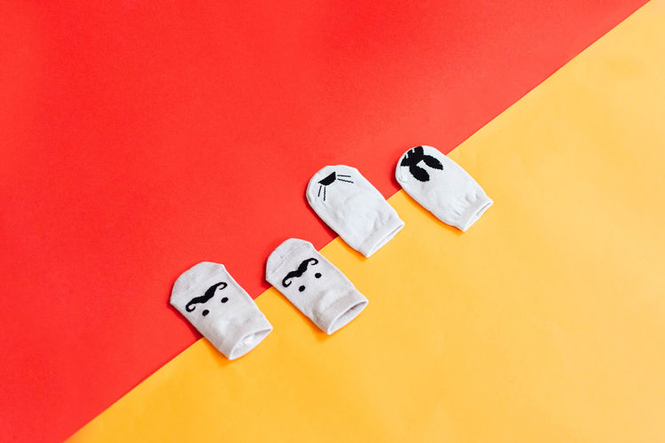 top view of four socks lay on the colorful background with red and yellow Baby Copy Space Day Flat Lay Indoors  Multi Colored Mustache No People Rabbit Red Socks Studio Shot Top View Tray Yellow Yellow Color