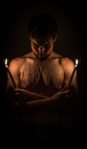 Shirtless man holding lit candle with wax on body against black background