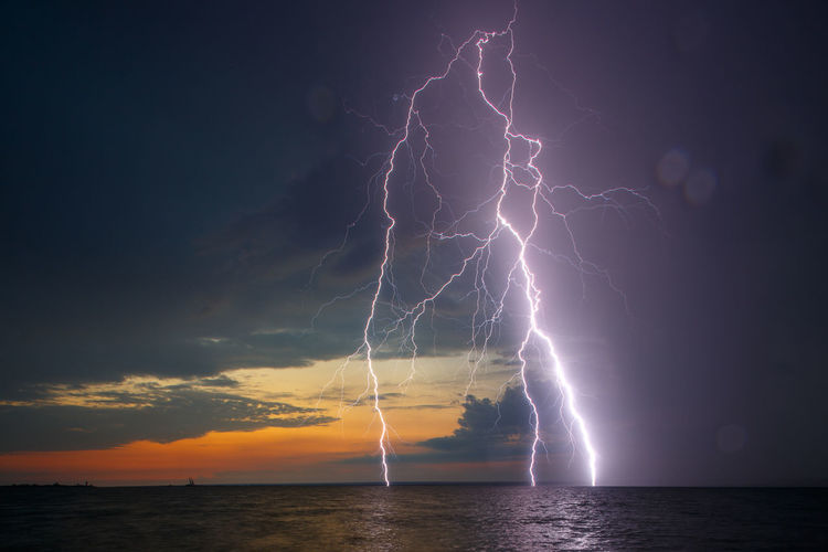 Lightning under the sea. Amazing natural thunderbolt. Purple electrical charge in the dar grey sky. Beauty In Nature Cloud - Sky Danger Day Dramatic Sky Forked Lightning Horizon Over Water Lightning Nature No People Outdoors Power In Nature Scenics Sea Sky Storm Storm Cloud Thunderstorm Tranquility Water Weather