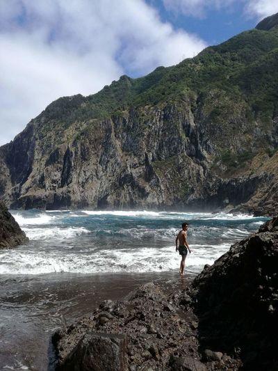 Shirtless man standing at beach against mountain