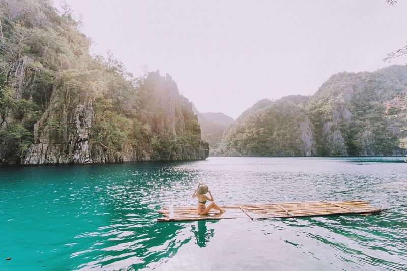 Side view of woman sitting on wooden raft in kayangan lake against sky