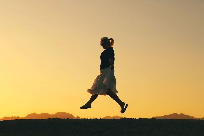 Side view of woman jumping against clear sky during sunset