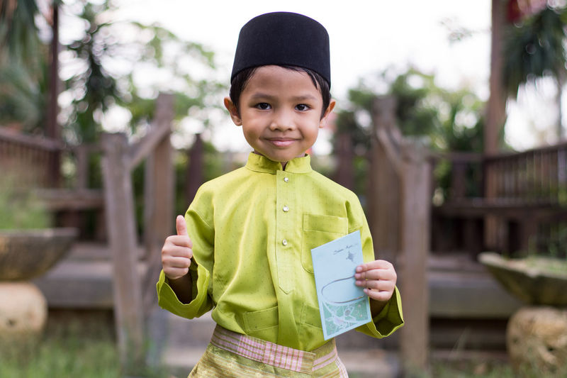 Portrait of cute boy in traditional clothing holding envelop
