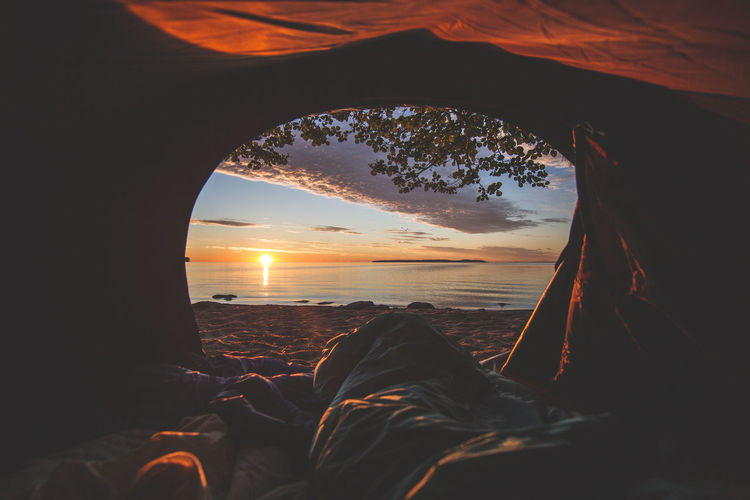 Scenic view of sea against sky during sunset seen through tent