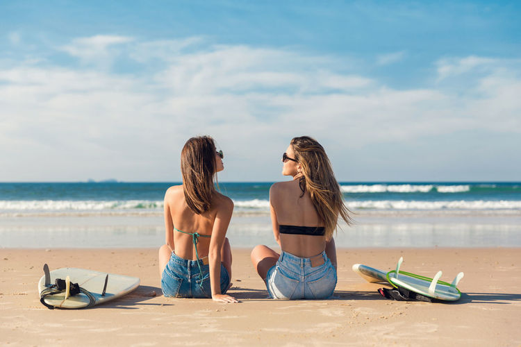 Rear view of female friends sitting at beach against sky