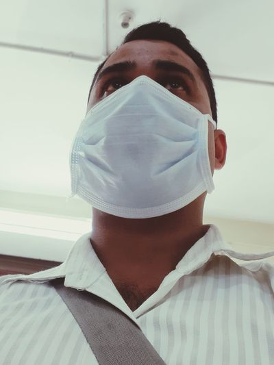 Low angle view of man wearing flu mask