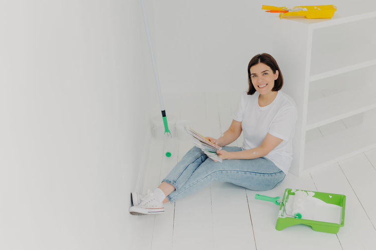Portrait of smiling woman holding swatch while sitting at new home