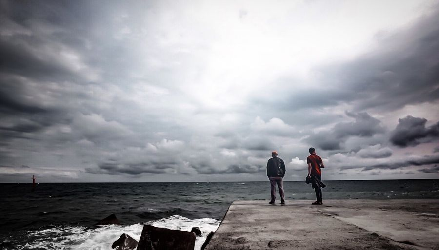 Male friends standing on pier over sea against cloudy sky