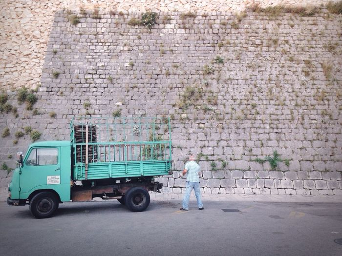 Senior Men Standing Near Truck Neat To Stone Wall