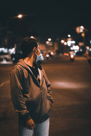 Full length of man standing on road at night