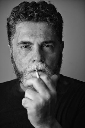Close-up portrait of a man smoking cigarette