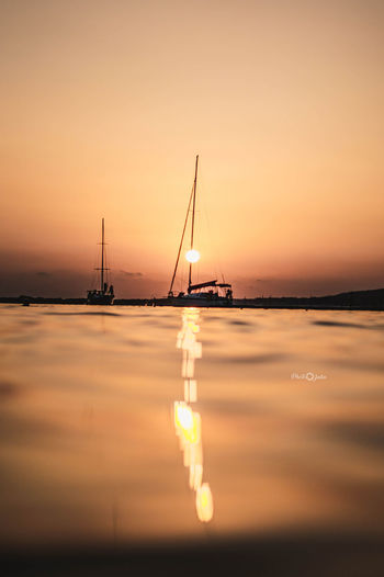 Photpgrapher JuliaVidyapina JReshetnyаk Nikon D3200 Sunset Reflection Water Tranquility Standing Water Beauty In Nature Tranquil Scene Sea Idyllic Nature Business Finance And Industry No People Scenics Industry Outdoors Sky Nautical Vessel Horizon Over Water Fog Sailboat