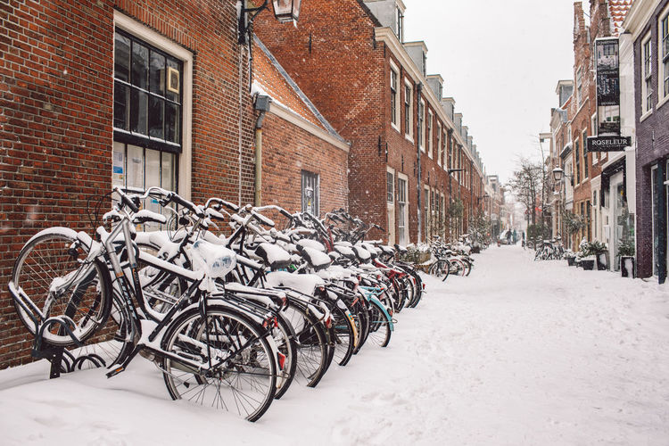 Bicycles on street amidst buildings during winter