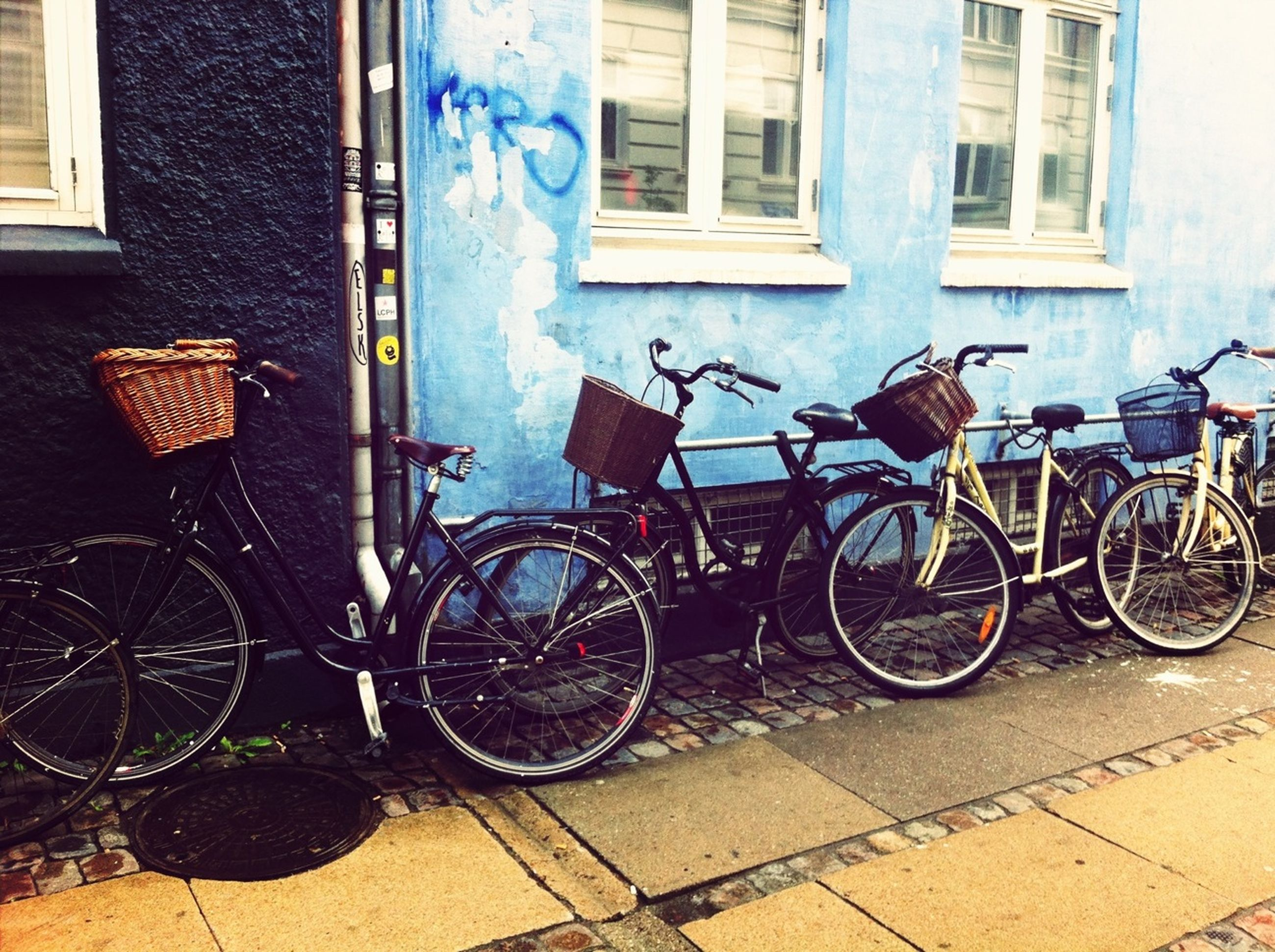 bicycle, building exterior, architecture, built structure, stationary, parking, wall - building feature, transportation, parked, sidewalk, land vehicle, window, mode of transport, house, wall, cobblestone, door, graffiti, building, day