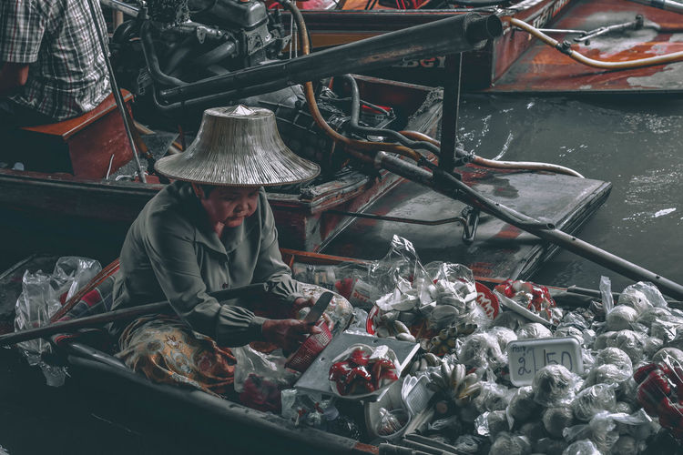 High angle view of senior woman selling food at floating market