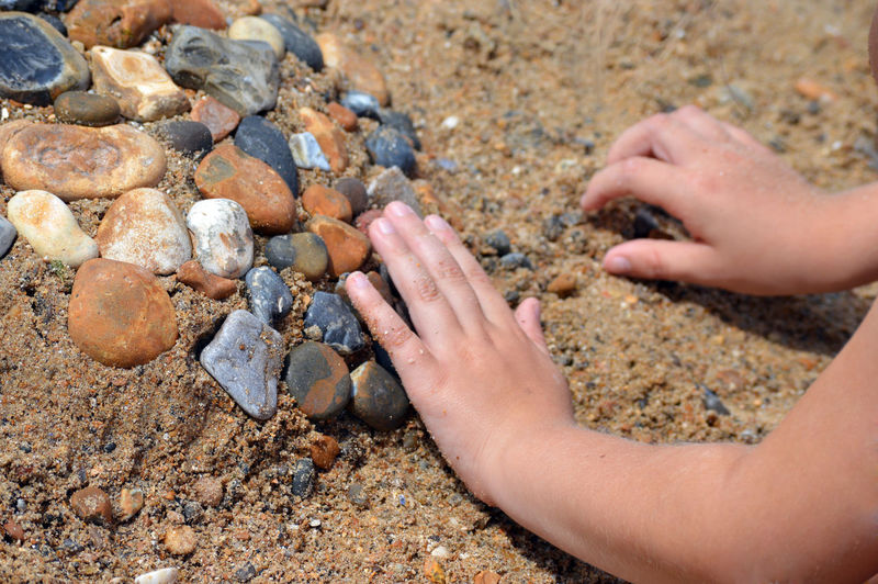 Close-up of hands on rocks at beach