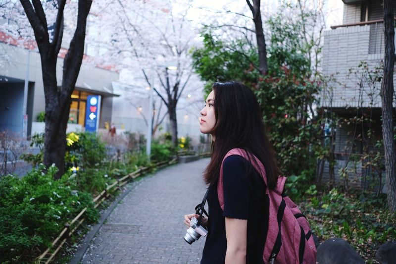Side view of young woman against plants