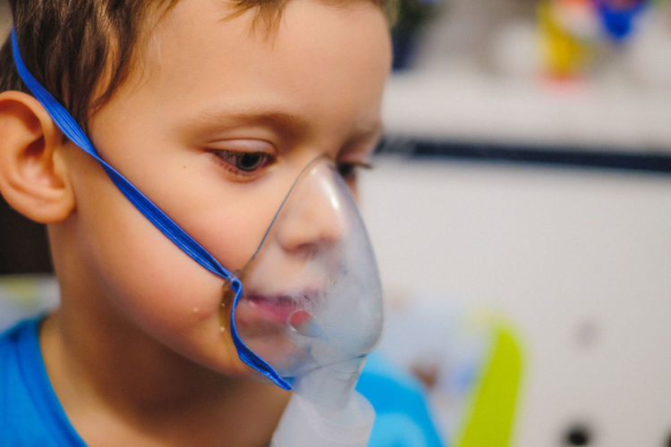 Close-up of boy wearing oxygen mask in hospital