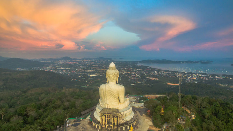 Rear View Of Giant Buddha Statue Against Cloudy Sky