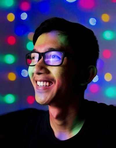 Portrait of smiling young man. man smiling with colorful light effect
