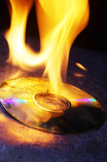 cd on fire Burning Compact Disc Flame Burning Cd Close-up Communication Fire Fire - Natural Phenomenon Flame Glowing Heat - Temperature History Illuminated Indoors  Motion No People Orange Color Outdated Outdated Tech Storage Warning Sign
