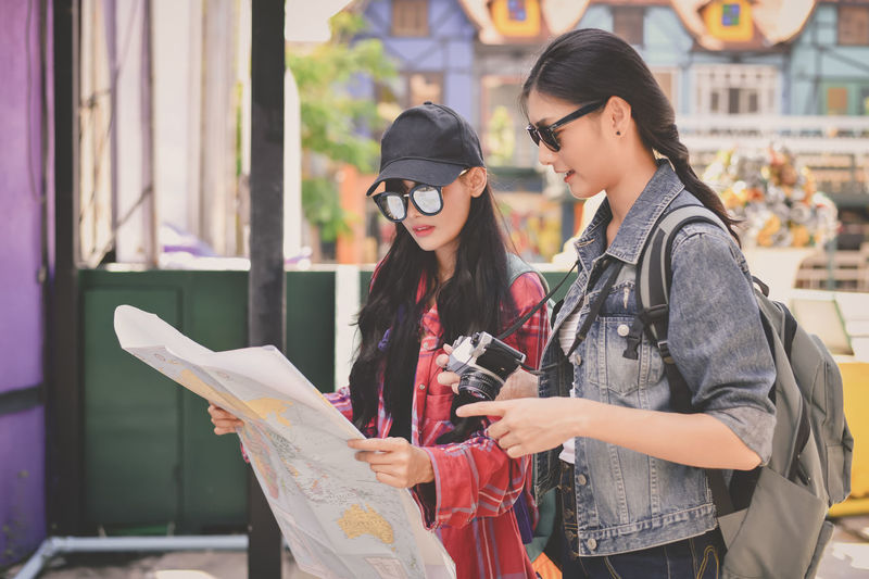 Friends in sunglasses reading map while standing outdoors