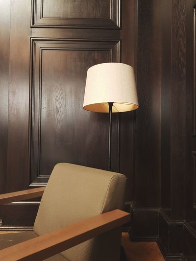 Empty armchair and floor lamp against wooden wall at home