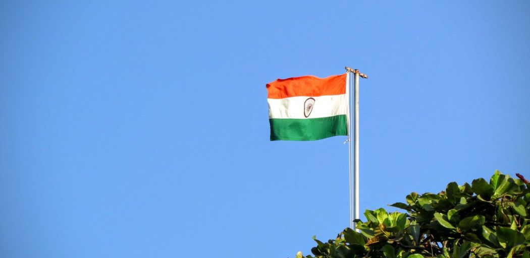Low angle view of indian flag by tree against clear blue sky