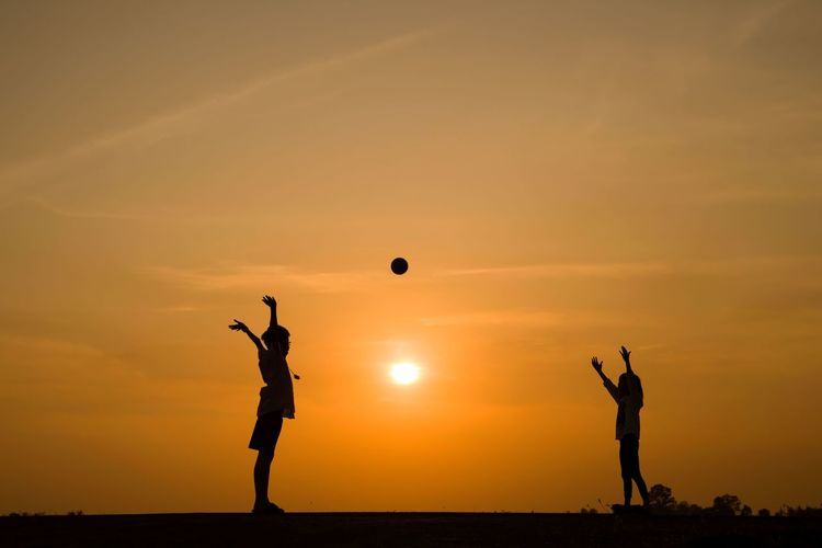 Silhouette friends playing on field during sunset
