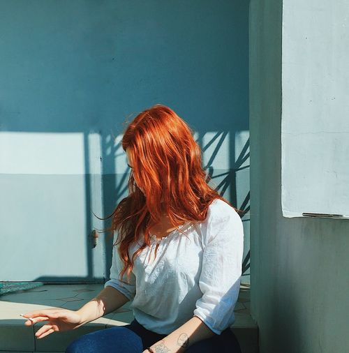 Woman sitting by wall