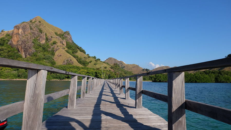 a beautiful island with wood quayside Quayside Beauty In Nature Blue Clear Sky Day Dock Indonesia Photography  Mountain Mountain Range Nature No People Outdoors Quay Railing Scenics Sea Shadow Sky Sunlight Water Wood - Material