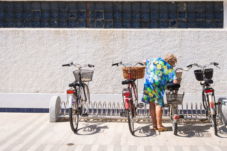 Woman Standing Amidst Bicycles Against Building