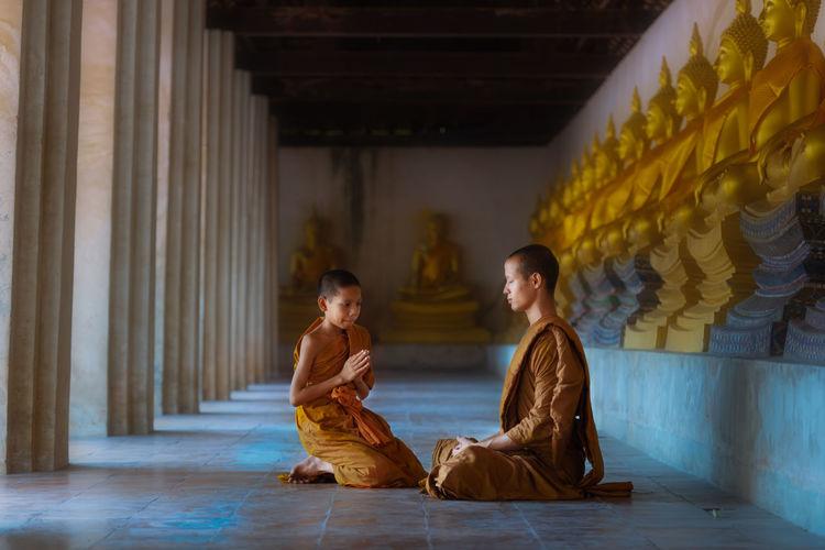 Boy kneeling by monk in buddhist temple