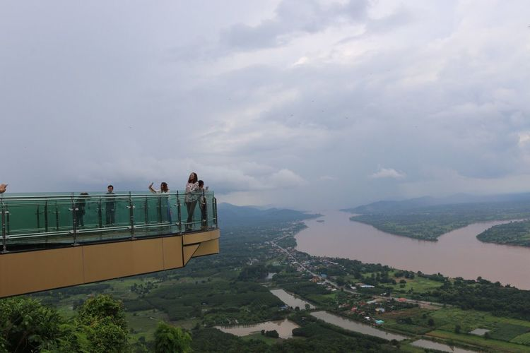Tourists on skywalk at wat pha tak suea with mekong river in background